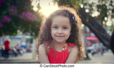 Close-up portrait of a happy cute little girl with curly hair in a red dress, sits in the park and looks at the camera on the sunset background. Stock footage.