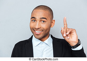 Close-up portrait of a happy man pointing finger up