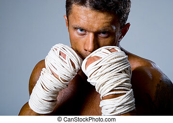 Close-up portrait of a kick-boxer in a fighting stance....