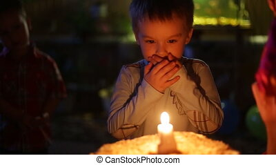 Close-up portrait of a little boy blows out the candles on the cake