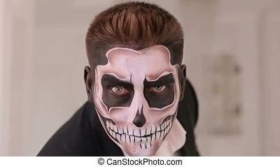 Close-up portrait of a man with a skull makeup. Dia de los muertos.