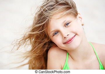 Close-up Portrait of a nice little girl with waving in the wind long hair sitting on the beach