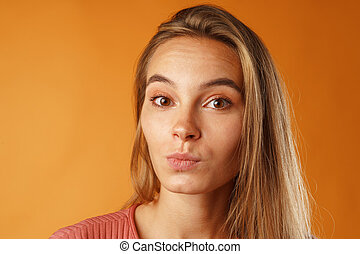 Close up portrait of a nice young woman with long blonde hair.
