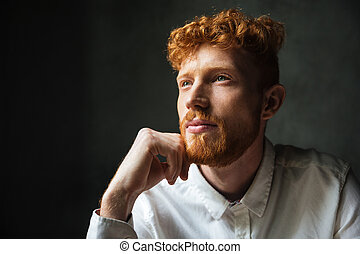 Close up portrait of a pensive young redhead man looking...