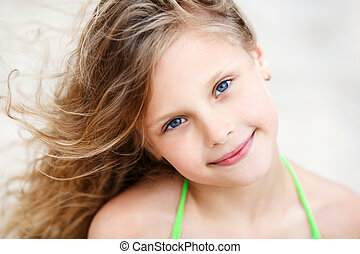 Close-up Portrait of a pretty smiling little girl with waving in the wind long hair