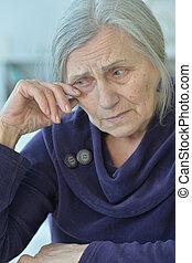 Close-up portrait of a sad elderly woman