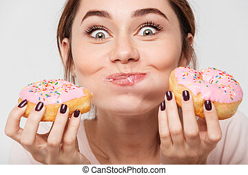 Close up portrait of a satisfied pretty girl eating donuts