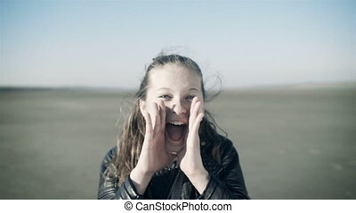 Close-up portrait of a screaming girl in the open space. The...