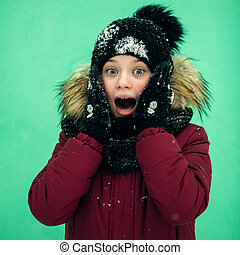 Close-up portrait of a screaming shocked teenage girl outdoors in winter.