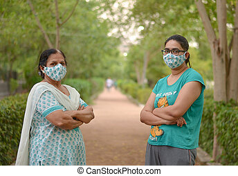 Close up Portrait of a senior Indian lady and young lady wearing matching surgical cotton mask to protect themself from Corona Virus (COVID-19) pandemic with hands folded / crossed in a park in India