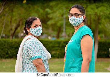 Close up Portrait of a senior Indian lady and young lady wearing matching surgical cotton mask to protect themself from Corona Virus (COVID-19) pandemic in a park in New Delhi, India
