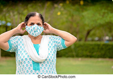Close up Portrait of a senior Indian lady and young lady wearing surgical cotton mask matching with her salwar kameez to protect herself from Corona Virus (COVID-19) pandemic, getting ready in India