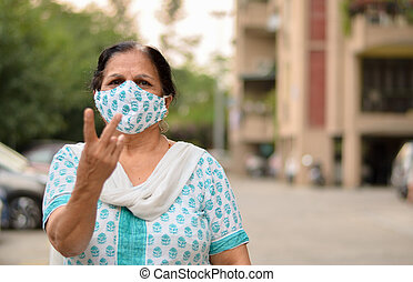 Close up Portrait of a senior Indian lady wearing surgical cotton mask matching with her salwar kameez to protect herself from Corona Virus (COVID-19) pandemic showing V (victory) sign in India