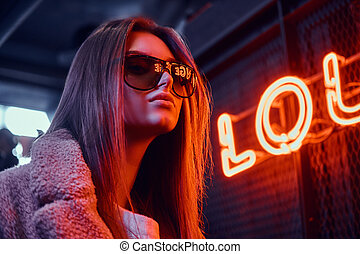 Close-up portrait of a sensual young girl wearing sunglasses and coat standing at the cafe with the industrial interior, a backlit signboard in the background