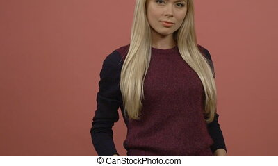 Close up portrait of a serious blond girl, wearing maroon shirt, standing against pink wall and staring at the camera.