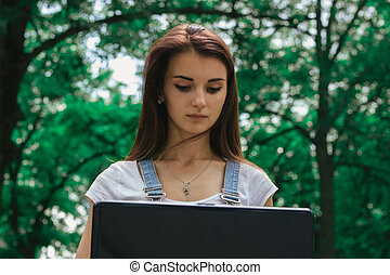 close-up portrait of a serious young Brunettes with a laptop