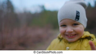 Close-up portrait of a small beautiful smiling boy with big eyelashes in a cap and yellow jacket looking directly at the camera.