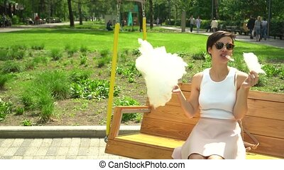 portrait of a smiling excited girl holding cotton candy at...