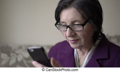 Close up portrait of a style old woman holding phone and...