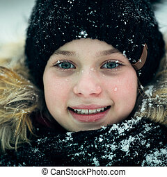 Close-up portrait of a teenage girl outdoors in winter.