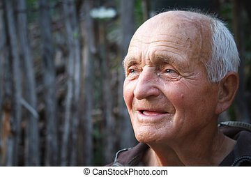 Close-up portrait of a very old man against the background of wattle, selective focus