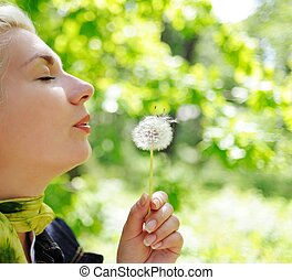 Close-up portrait of a woman blowing to dandelion flower