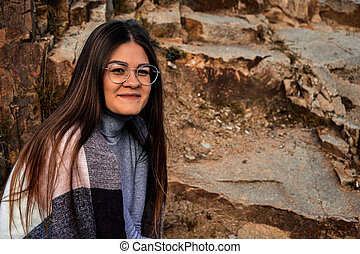 Close-up portrait of a woman in eyeglasses, with scarf on the lake. Outside. Happy smiling girl