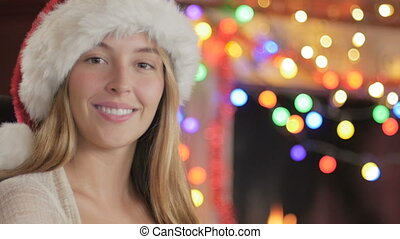 Close up portrait of a woman wearing a Santa hat in front of a fireplace