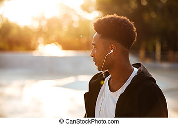 Close up portrait of a young african man in earphones