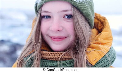 Close-up portrait of a young beautiful teenage girl girl with blond hair blowing the wind, enjoying winter day outdoors