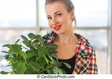 Close-up portrait of a young beautiful woman, holding decorative plant, smiling, looking at camera