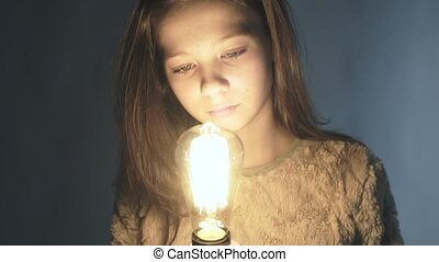 Close-up portrait of a young girl holding a glowing light bulb in her hands.