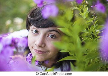 Close-up portrait of a young girl in the garden among the flowers.