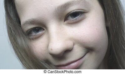 Close-up portrait of a young girl looking in the camera and smiling in slowmo.