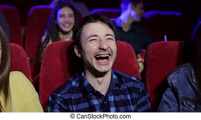 Close-up portrait of a young laughing man in a movie theater.