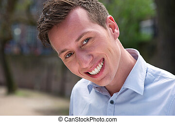 Close up portrait of a young man smiling outdoors