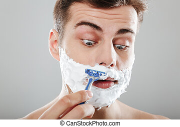 Close up portrait of a young man with shaving foam
