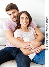 Close-up portrait of a young smiling couple sitting