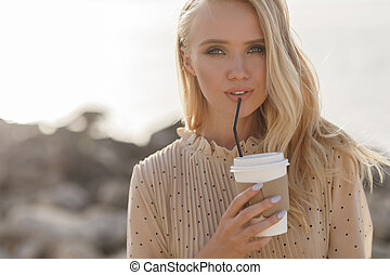Close up portrait of a young smiling woman with coffee outdoor