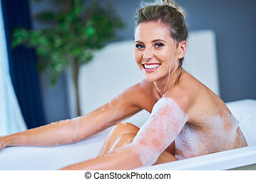 Close-up portrait of a young woman relaxing in the bathtube...