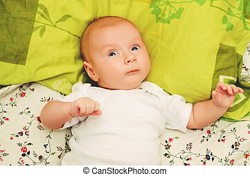 Close up portrait of adorable 4-5 month old baby lying on a pillow