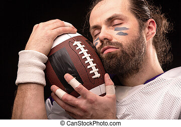 Close up portrait of American Football Player with ball