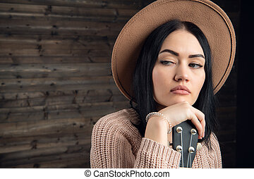 Close up portrait of an attractive brunette woman wearing sweather and hat with beautiful guitar. Wooden background, studio