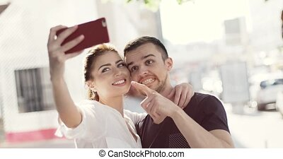 Close up portrait of an attractive young couple on holiday, posing for self portraits outdoors in the city. Love and technology lifestyle, outdoors.