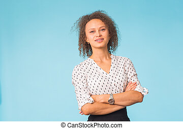 Close up portrait of an attractive young mixed race woman over blue background with copy space