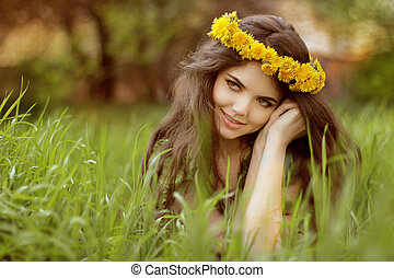 Close-up portrait of an attractive young woman outdoors, lying in the grass, relaxing