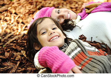 Close-up portrait of an beautiful autumn woman and kid laying on ground