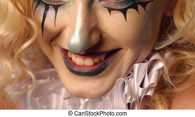 Close-up portrait of an excited blonde woman with make-up in halloween.