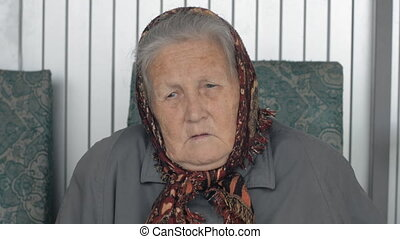 Close-up portrait of an old woman in a brown kerchief.