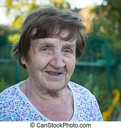 Close-up portrait of an old woman, outdoors.